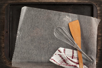 Old metal baking pan with paper and kitchen utensils