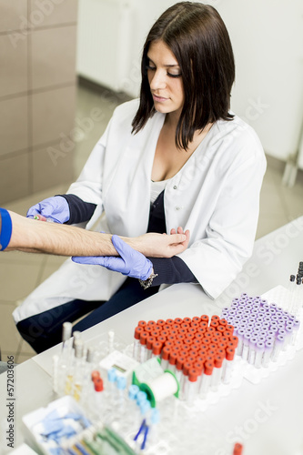 Young woman doing blood sampling in modern medical laboratory