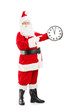 Full length portrait of a Santa Claus pointing on a clock