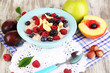 Oatmeal in plate with berries on napkins on wooden table