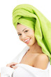 Attractive woman with a green towel on her head and bathrobe