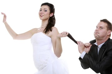 Emancipation idea. Woman pulling on mans tie, funny couple