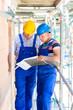 Handwerker kontrollieren Pläne auf einer Baustelle