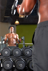 Mirror reflection of two men exercising in gym