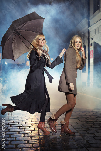 Two blonde ladies running during rain