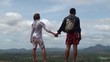 Young couple of tourists stands in the wind on top of a mountain