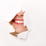 toothy smile of cheerful teen girl through hole of white