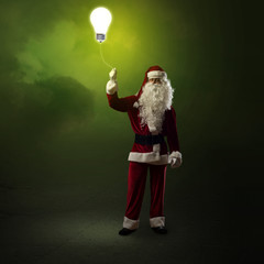Santa Claus is holding a shining lamp