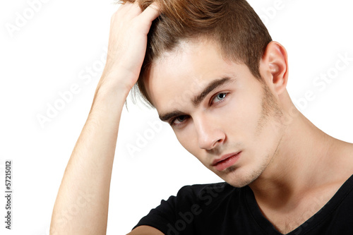 Handsome young man touching his hair, portrait of sexy guy looki