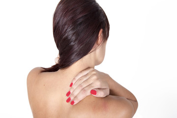 Brunette woman massaging her shoulder because it hurts.