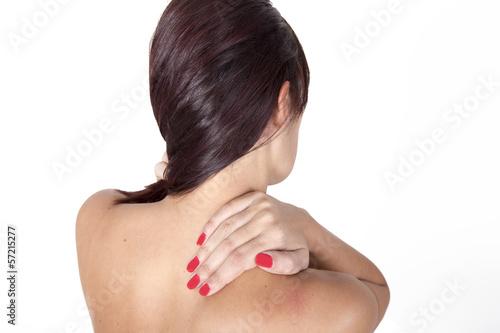 Brunette woman massaging her shoulder because it hurts.