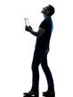 man holding digital tablet  looking up silhouette