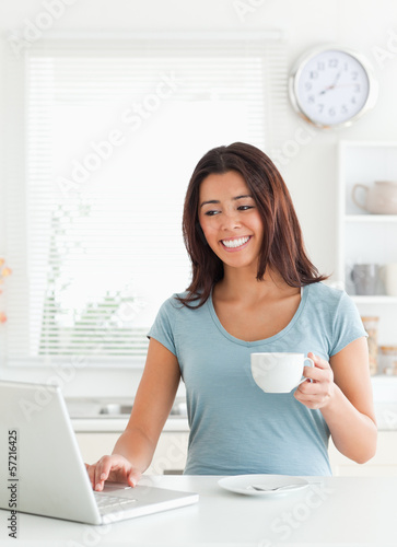 Charming woman enjoying a cup of coffee while relaxing with her