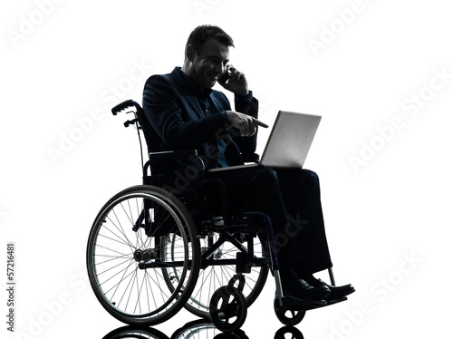 handicapped business man computing laptop computer  in wheelchai