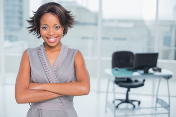 Smiling businesswoman standing in office and crossing her arms