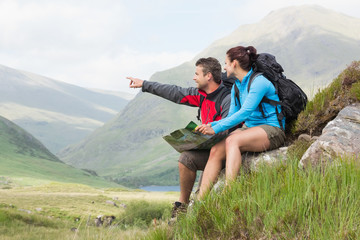 Couple taking a break after hiking uphill and holding map