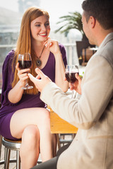 Smiling woman having glass of wine with her boyfriend