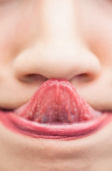 Extreme close up on woman touching her nose with her tongue