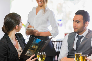 Businesswoman ordering dinner from smiling waitress