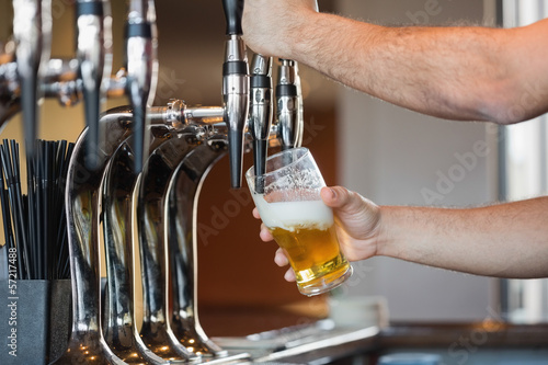 Barmans arms pulling a pint of beer