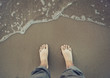 Picture of male bare foot near the sea water
