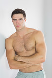 Focused handsome man leaning topless against wall