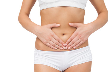 Mid section of slim woman touching her belly with her hands
