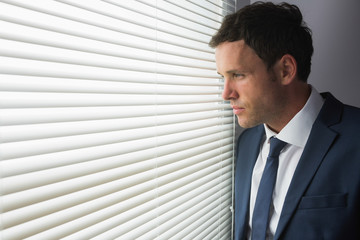 Serious handsome businessman looking out of window