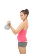 Peaceful sporty brunette holding grey and pink kettlebell