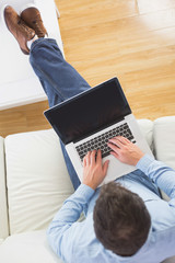 High angle view of casual man typing on laptop with feet on tabl
