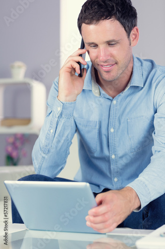 Happy casual man using tablet and phoning