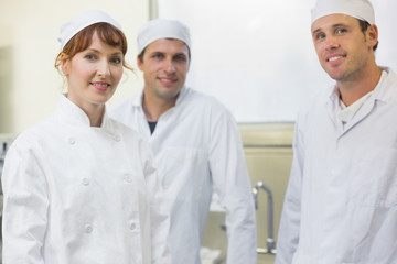 Three bakers posing in a kitchen