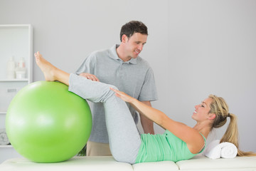 Patient holding exercise ball with legs