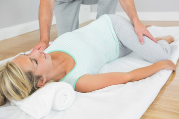 Physiotherapist checking patients hips on a mat on the floor
