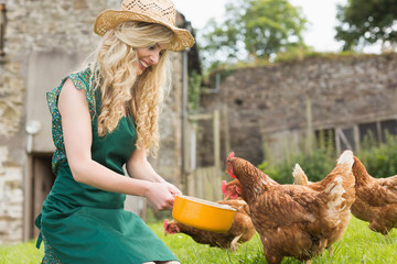 Young woman feeding her chickens