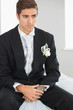 Young handsome bridegroom sitting on bed