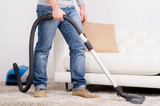 Vacuum Cleaner. A man does house work with a vacuum cleaner