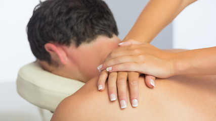 Physiotherapist massaging male patient with hands
