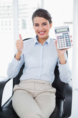 Cheering classy brown haired businesswoman showing her calculato