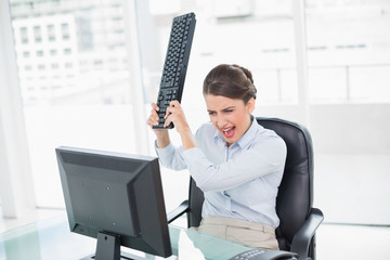 Furious classy brown haired businesswoman throwing her keyboard