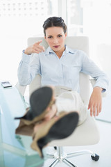 Frowning stylish brunette businesswoman relaxing with feet up