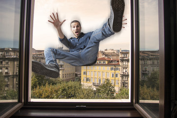 young man falling down a window