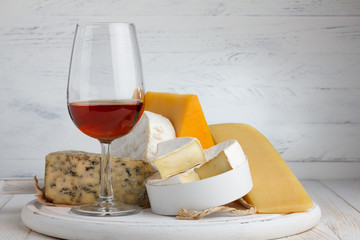 Cheese and red wine on wooden table still life