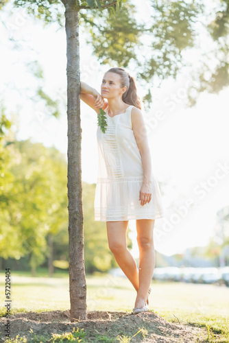 Portrait of thoughtful young woman standing near seedling tree