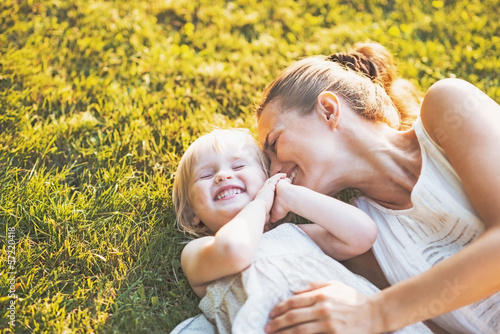 Happy mother and baby laying on meadow - 57220418
