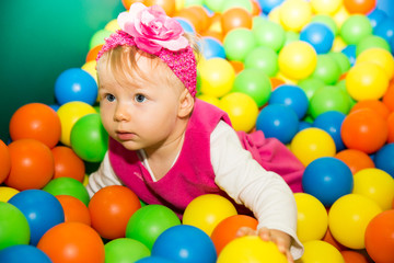 Happy child girl in colored ball on playground