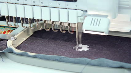 Machine embroidery working a soccer ball on jeans