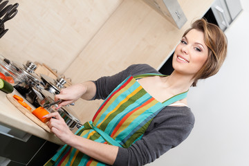 Pretty woman in striped apron cuts vegetables