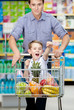 Little boy with fists up suiting in shopping trolley with food