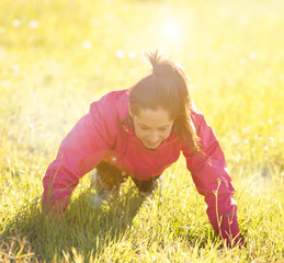Pretty woman exercising on a meadow